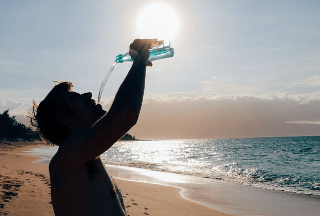 man drinking water at beach